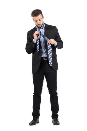 vistiendose: Hombre de negocios joven barbudo vistiendo. Cuerpo completo retrato de cuerpo entero aisladas sobre fondo blanco de estudio. Foto de archivo