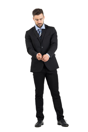 formal dressing: Bearded young man in suit buttoning sleeves looking down. Full body length portrait isolated over white studio background.