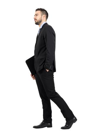 persona caminando: barbudo hombre de negocios joven en el juego que sostiene la carpeta de archivos con vista lateral de la documentación a pie. la longitud del cuerpo Retrato completo aislado sobre fondo blanco del estudio. Foto de archivo