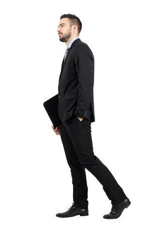 Young bearded businessman in suit holding file folder with documentation walking side view. Full body length portrait isolated over white studio background.