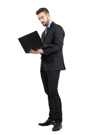 Young standing business man working on a laptop. Full body length portrait isolated over white studio background.