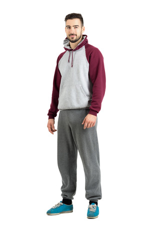 hoodie: Young bearded male in sport casual clothes smiling looking at camera. Full body length portrait isolated over white studio background. Stock Photo