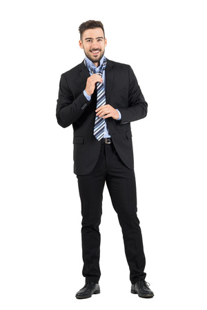 formal dressing: Young elegant businessman in suit tying and adjusting necktie. Full body length portrait isolated over white studio background. Stock Photo