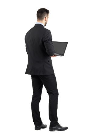 back screen: Rear view of young man in suit using laptop.  Full body length portrait isolated over white studio background. Stock Photo