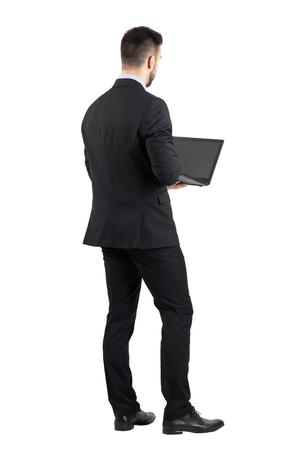 personas de espalda: Vista trasera de un joven en juego usando la computadora port�til. la longitud del cuerpo Retrato completo aislado sobre fondo blanco del estudio. Foto de archivo