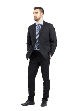 looking  up: Businessman in suit with hands in pockets smiling and looking away. Full body length portrait isolated over white studio background.