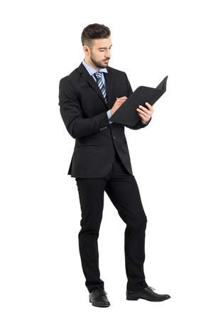cuerpo hombre: documento de negocios que firma joven de confianza. la longitud del cuerpo Retrato completo aislado sobre fondo blanco del estudio. Foto de archivo
