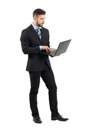 Side view of young businessman in suit using laptop.  Full body length portrait isolated over white studio background. Standard-Bild