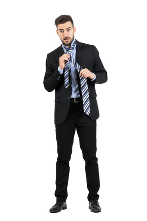 formal dressing: Bearded young corporate man tying necktie looking at camera. Full body length portrait isolated over white studio background. Stock Photo