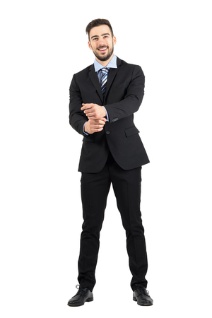 spontaneous: Spontaneous laughing man in suit looking at camera adjusting sleeves. Full body length portrait isolated over white studio background.