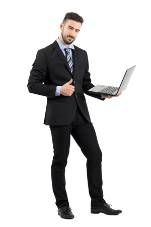 Smiling happy businessman with laptop showing thumb up gesture looking at camera.  Full body length portrait isolated over white studio background.