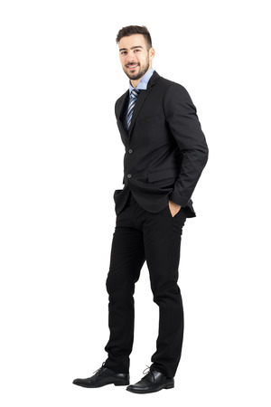 over white: Confident happy business man with hands in pocket side view.  Full body length portrait isolated over white studio background.
