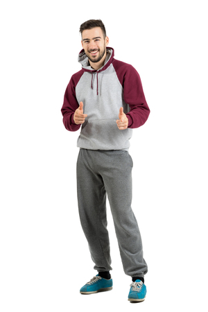 hoodie: Bearded smiling young man in casual sportswear pointing finger gun hand gesture at camera. Full body length portrait isolated over white studio background.