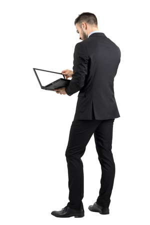 Rear view of businessman working on a laptop with blank empty screen. Full body length portrait isolated over white studio background.