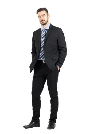 Young confident bearded business man in suit looking at camera.  Full body length portrait isolated over white studio background. 스톡 콘텐츠