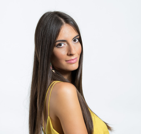 healthy looking: Portrait of young Latin woman with healthy long silky hair looking at camera over her shoulder on gray studio background. Stock Photo