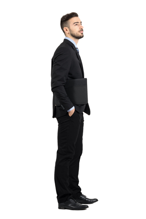 length: Young confident businessman holding documents folders looking away side view. Full body length portrait isolated over white studio background. Stock Photo