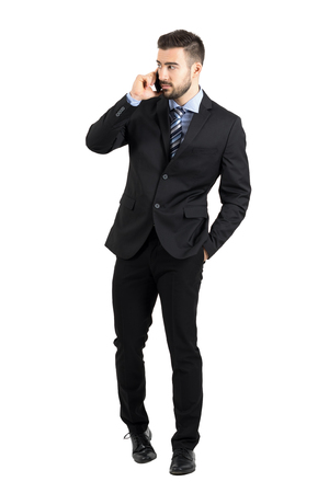over white: Young bearded businessman in suit talking on the phone walking towards camera looking away. Full body length portrait isolated over white studio background.