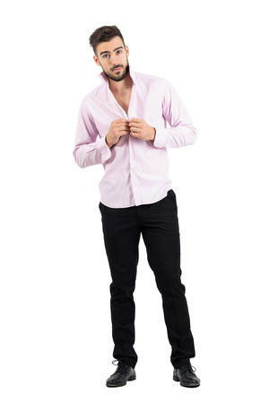 formal dressing: Young groom buttoning his pink shirt looking at camera.  Full body length portrait isolated over white studio background.