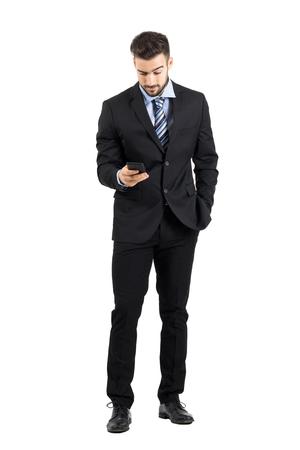 completos: Hombre de negocios joven en el mensaje de la lectura del juego en su teléfono celular. Cuerpo completo retrato de cuerpo entero aisladas sobre fondo blanco de estudio.