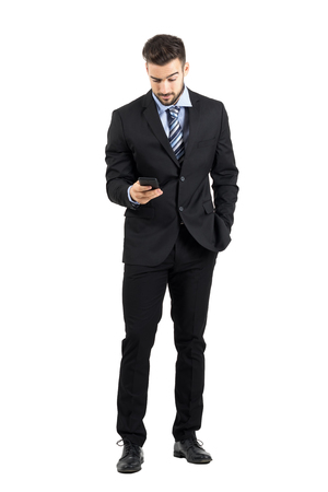 Young business man in suit reading message on his cellphone. Full body length portrait isolated over white studio background.