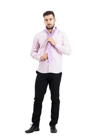 well dressed: Young elegant well dressed man in pink shirt adjusting and tying pink necktie knot. Full body length portrait isolated over white studio background.