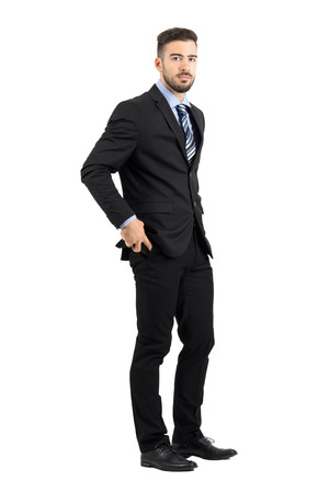business man phone: Serious young business man putting mobile phone in his pants pocket side view. Full body length portrait isolated over white studio background.