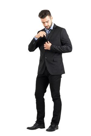 cuerpo hombre: Hombre de negocios joven que pone el teléfono móvil en el bolsillo interior de la chaqueta del traje. Cuerpo completo retrato de cuerpo entero aisladas sobre fondo blanco de estudio. Foto de archivo