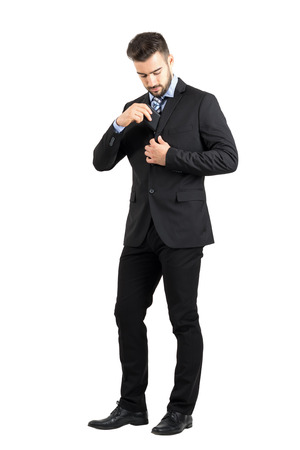 put: Young business man putting cellphone in his suit jacket inner pocket. Full body length portrait isolated over white studio background.
