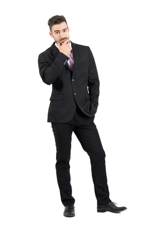 over white: Doubtful young business man with hand on his chin looking at camera. Full body length portrait isolated over white studio background. Stock Photo
