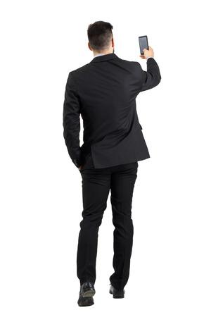 Geschäftsmann im Anzug für gutes Handy Signal Rückansicht der Suche oder Foto. Ganzkörper-Länge Porträt über weißem Hintergrund Studio isoliert. Lizenzfreie Bilder