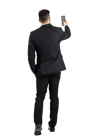 Businessman in suit searching for good phone signal rear view or taking photo. Full body length portrait isolated over white studio background. Stockfoto