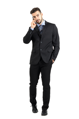 looking towards camera: Handsome young businessman on the phone looking and walking towards camera. Full body length portrait isolated over white studio background.