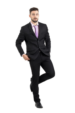 cool man: Cool young handsome man in suit discretely shining shoes on his pants. Full body length portrait isolated over white studio background. Stock Photo