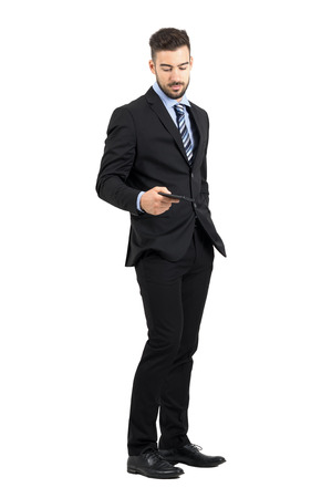 Handsome businessman taking cellphone from his pocket side view. Full body length portrait isolated over white studio background. Stock Photo