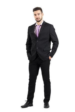 terno: El hombre con estilo joven conf�a en el juego que mira a la c�mara con las manos en los bolsillos. la longitud del cuerpo Retrato completo aislado sobre fondo blanco del estudio.