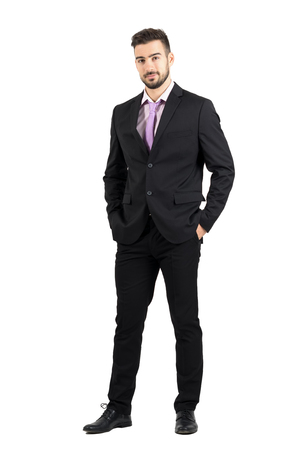 Confident young stylish man in suit looking at camera with hands in pockets. Full body length portrait isolated over white studio background. Stockfoto
