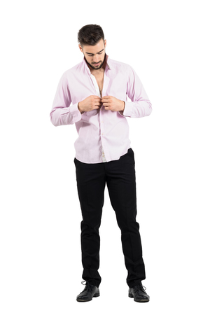 formal dressing: Young groom buttoning his pink shirt preparing for his wedding.  Full body length portrait isolated over white studio background.