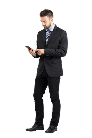 Young bearded business man typing message on smartphone touch screen. Full body length portrait isolated over white studio background.