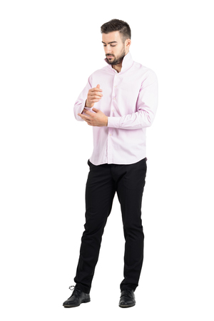 formal dressing: Young elegant man in pink shirt buttoning his sleeves. Full body length portrait isolated over white studio background.