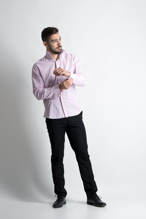 Young bearded groom buttoning his sleeve cuffs looking away. Full body length portrait over gray studio background.