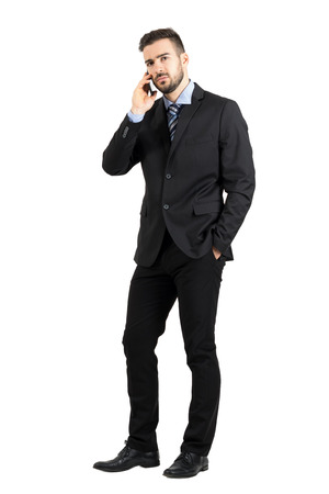 men in suit: Angry business man on the phone looking at camera. Full body length portrait isolated over white studio background.