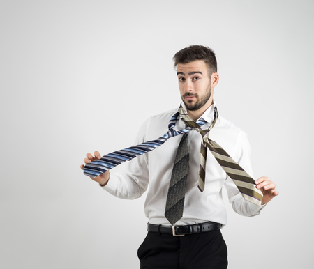 raised eyebrows: Portrait of a confused young bearded man in white shirt choosing right necktie over gray studio background.