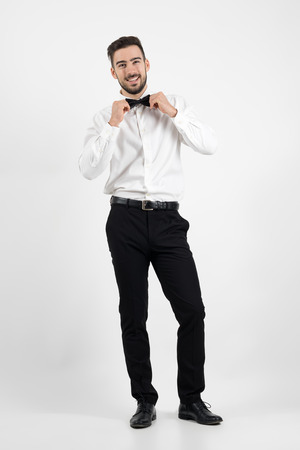 formal dressing: Laughing happy young bearded elegant man adjusting bow tie looking at camera. Full body length portrait over gray studio background.