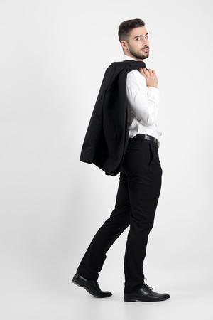 Charming elegant man walking carrying suit jacket over his shoulder. Side view.  Full body length portrait over gray studio background.