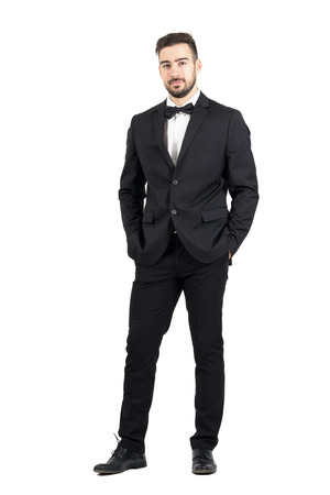 Wealthy confident relaxed young man in tuxedo looking at camera with hands in pockets. Full body length portrait isolated over white studio background. Stock Photo