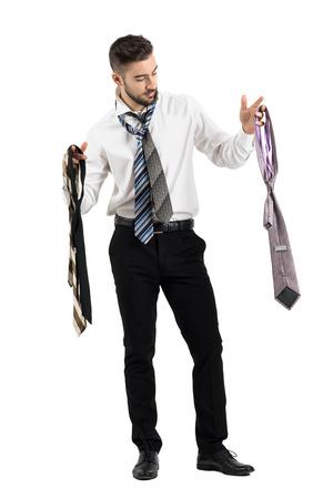 vistiendose: Hombre que consigue vestido elegir entre muchas corbatas. la longitud del cuerpo Retrato completo aislado sobre fondo blanco del estudio.