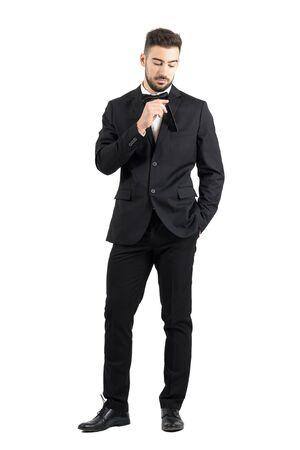 men standing: Young stubble man putting black plastic comb inside tuxedo pocket. Full body length portrait isolated over white studio background.