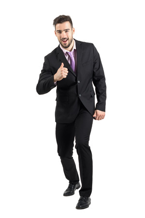 man in tuxedo: Excited businessman in suit with thumb up gesture smiling at camera. Full body length portrait isolated over white studio background. Stock Photo