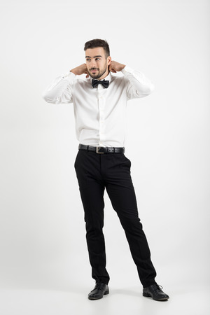 getting dressed: Young groom getting dressed adjusting bow tie looking away. Full body length portrait over gray studio background. Stock Photo